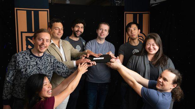 """Alcuni dei ricercatori di OpenAi stringono il computer portatile che ha sconfitto in una partita uno contro uno """"Dendi"""" allo scorso The International."""